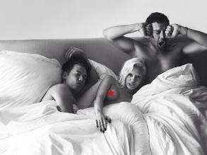 Miley Cyrus posa entre dos hombres acostada en una cama
