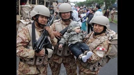 Entusiastas espectadores se toman fotos con los soldados en la Parada Militar