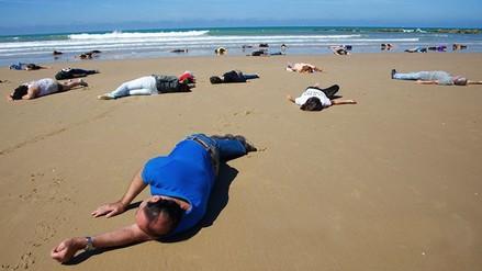 Fotos: Playa de España se cubre de 'cadáveres' en solidaridad con refugiados