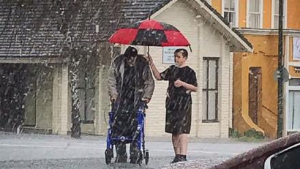 Adolescente ayuda a un anciano a cruzar la calle durante una tormenta