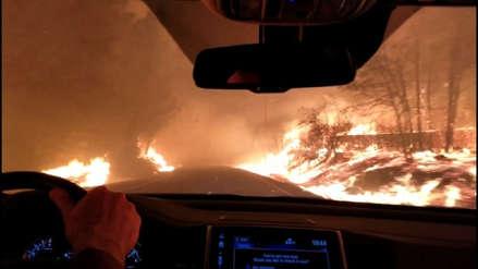 Una familia reza y maneja escapando de las llamas de incendio forestal en California