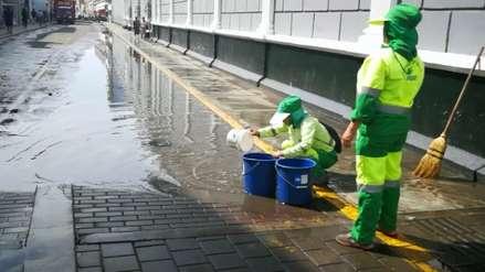 A falta de equipos trabajadores de limpieza retiran agua de lluvia con baldes y escobas