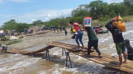 Piura: Vecinos de Malingas usan tablas como puente para cruzar las aguas