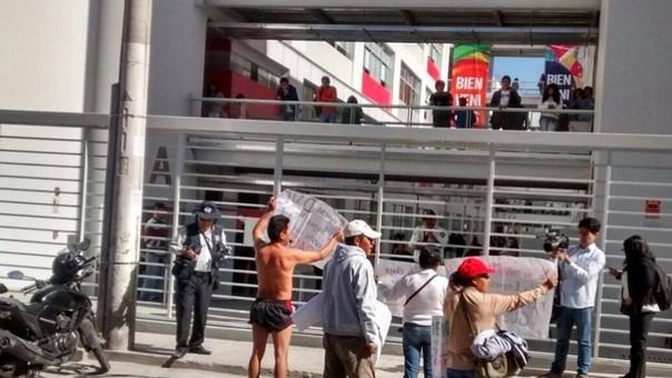Obrero protesta semidesnudo en puerta de universidad