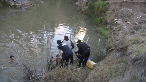Policía y grupo de rescate realizan denodados esfuerzos para recuperar el cuerpo del infortunado joven