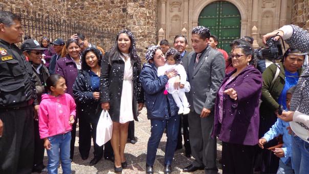 Ministra carga a su ahijada fuera del templo Santiago Apóstol de Lampa.