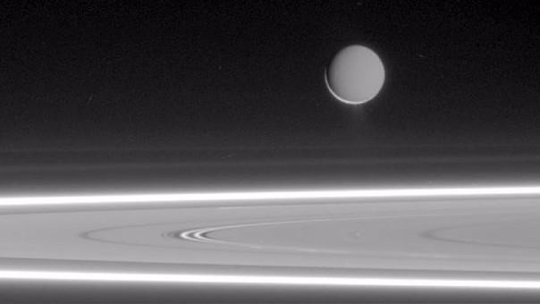 Encélado sobre los anillos de Saturno.
