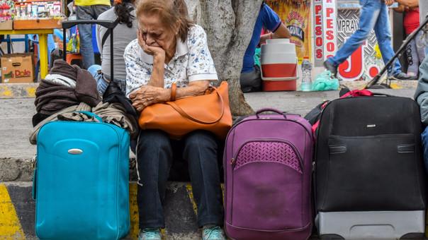 Una mujer espera sentada en una calle de Cúcuta.