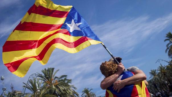 Dos manifestantes se abrazan durante la concentración convocada esta tarde en apoyo a la declaración unilateral de independencia, en el Paseo de Lluis Companys, frente al parque de la Ciutadella de Barcelona.