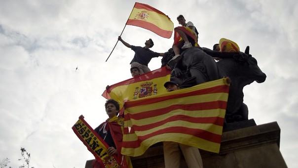 Un grupo de catalanes agita banderas de su región y de España en una protesta a favor de la unidad de su país.