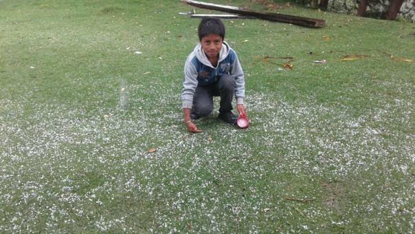 Niño juega con granizo tras lluvia