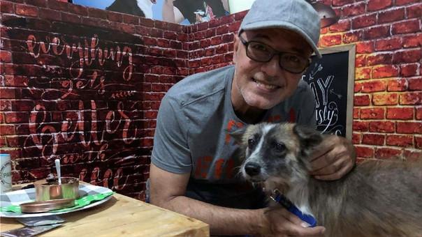 Fotografía de un hombre filipino junto con un perro en la sede de PAWS.