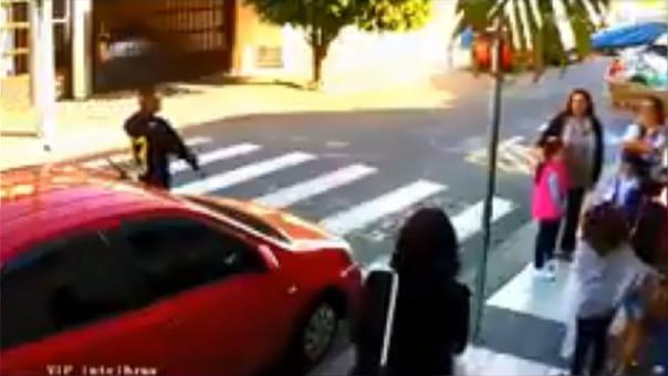 El delincuente, detrás del carro rojo, momentos antes de sacar el arma y amenazar a las madres de familia.
