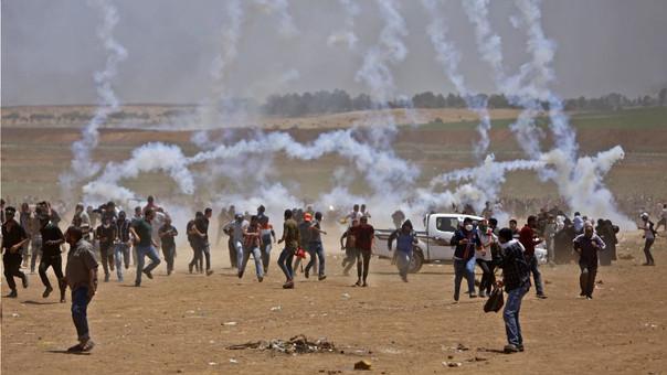 Palestinos corren para cubrirse del gas lacrimógenos lanzado por el Ejército de Israel en Gaza.