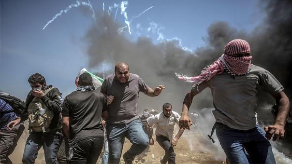 Manifestantes se protegen del gas lacrimógeno en Gaza.