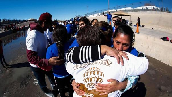 Indocumentados mexicanos se abrazan en la frontera con Estados Unidos.
