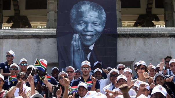 El capitán de la selección sudafricana de cricket, Faf du Plessi, posea con escolares durante una ceremonia por los 100 años de Nelson Mandela.