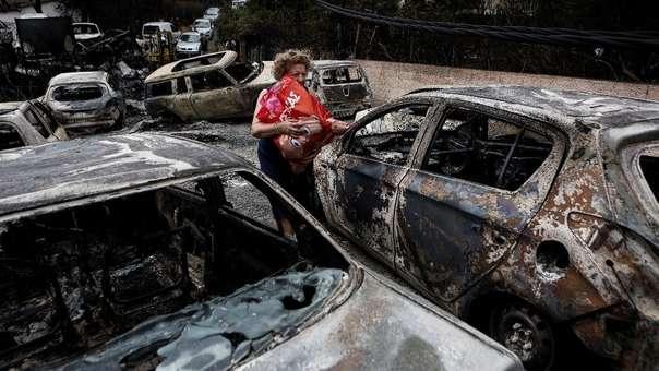 Una mujer cargas sus pertenencias entre los restos de autos calcinados en el incendio.