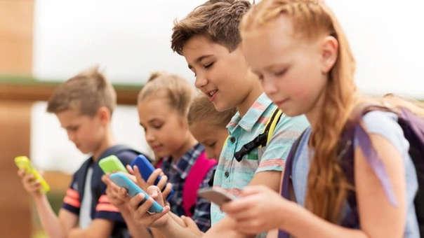 Niños utilizan sus teléfonos celulares en la escuela.
