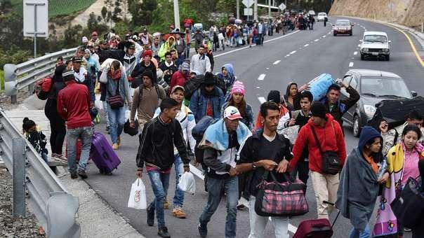 Migrantes venezolanos en ruta a Perú caminan por la carretera Panamericana en Tulcán, Ecuador, luego de cruzar la frontera con Colombia.