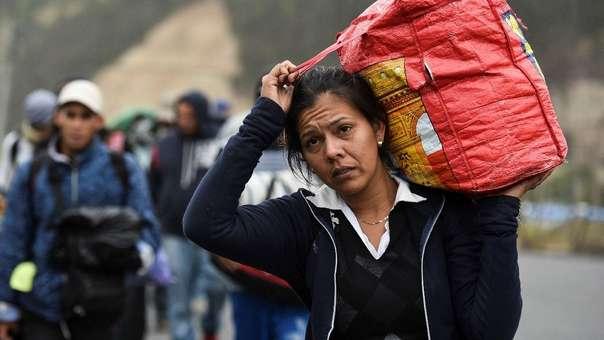 Una inmigrante venezolana carga su mochila y se abriga en medio del frío en Tulcan, mientras camina por la Panamericana en su ruta hacia Perú.