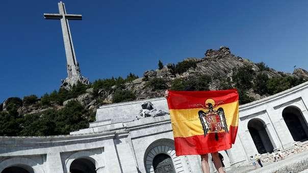 Una persona despliega una bandera anticonstitucional, vinculada al franquismo, en la explanada del Valle de los Caídos, donde están los restos del dictador Francisco Franco.