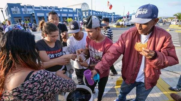 Venezolanos reciben comida de parte de voluntarios mientras esperan que se autorice su ingreso al Perú a través de Tumbes.