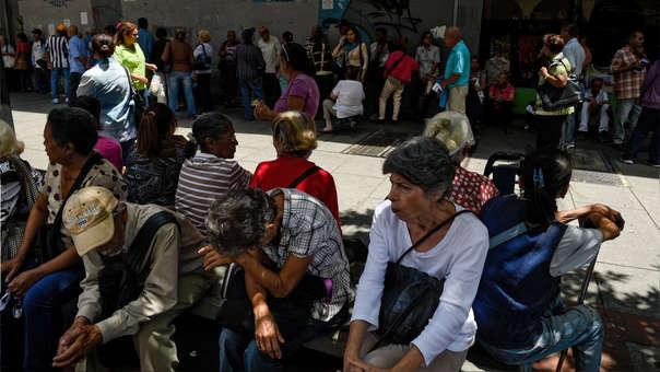 Ciudadanos hacen cola para retirar parte de sus pensiones en un banco de Caracas.
