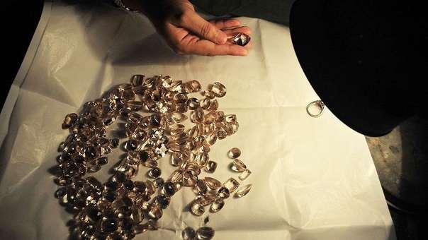 Un hombre revisa una colección de joyas.
