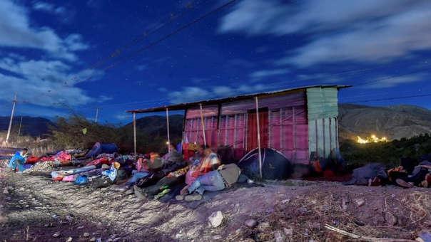 Migrantes venezolanos duermen en la carretera que divide Perú con Ecuador.