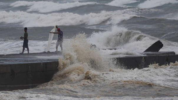 Hombres pescan en la orilla antes de la llegada del tifón.
