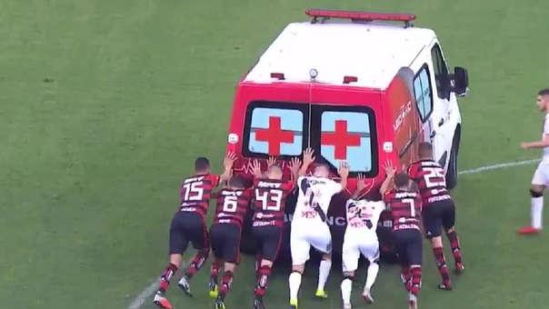 Jugadores de ambos equipos se unen para empujar una ambulancia.
