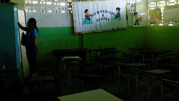 Una maestra está parada cerca de una pizarra que da la bienvenida a clases y de pupitres vacíos.