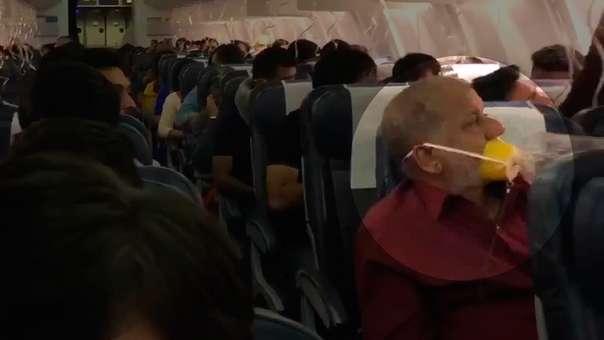 En el avión se observa a un hombre usando mal la mascarilla de oxígeno.