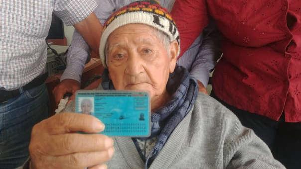 El anciano muestra su documento de identidad que certifica que tiene 102 años de edad.