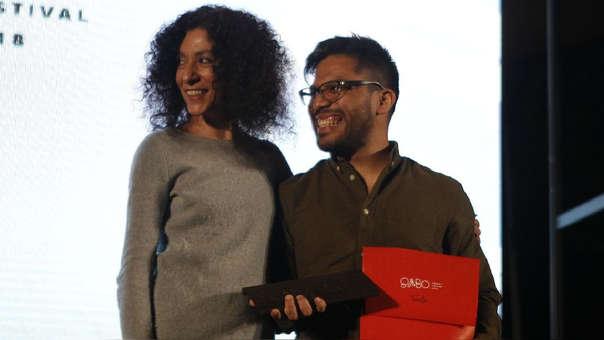 El periodista peruano Joseph Zárate (derecha) posa con su premio hoy durante la ceremonia de premiación.