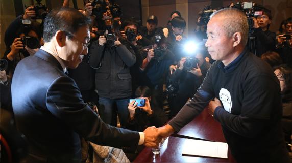 El copresidente de Samsung Electronics, Kim Ki-nam (izquierda), le da la mano a Hwang Sang-gi (derecha), líder de los familiares de las víctimas.