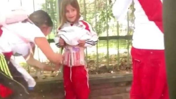 La mujer encubre los pirotécnicos en el cuerpo de la niña para al parecer hacerlos ingresar al estadio Monumental de River Plate.