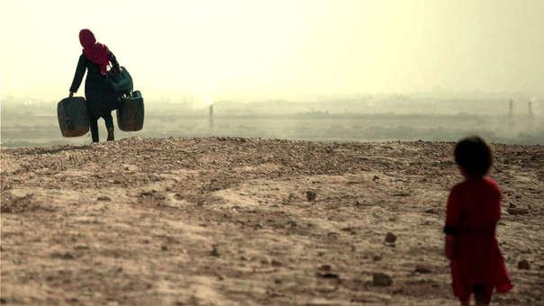 Una mujer camina por el desierto para buscar agua. Detrás, una niña la observa.