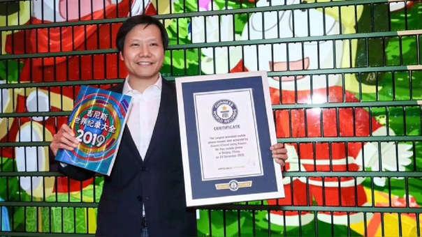 Lei Jun, CEO de Xiaomi, sostiene el certificado de Guinness frente al mural navideño armado con más de mil smartphones