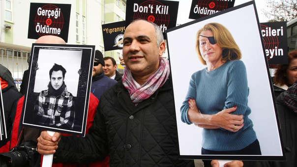 Hombre protesta por la muerte de los periodisats Rémi Ochlik (izquierda) y Marie Colvin (derecha).