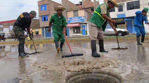 Obreros echando agua al buzón