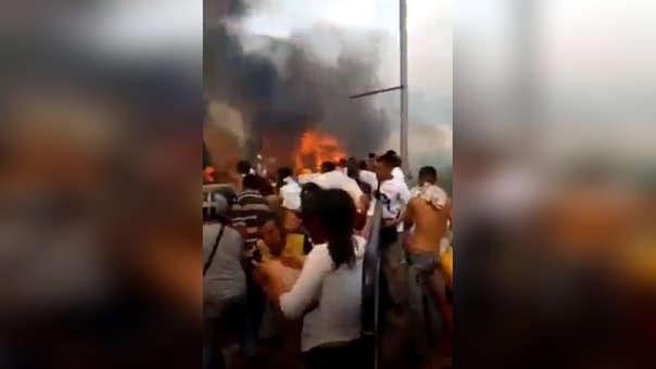 Ciudadanos venezolanos presencian la quema de la ayuda humanitaria.