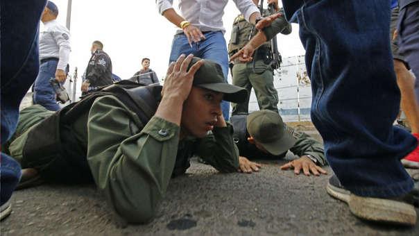 Dos soldados venezolanos yacen en el suelo tras entrar a Colombia para desertar.