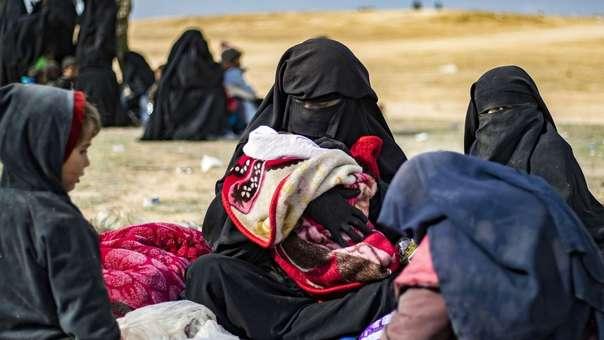 La esposa de un yihadista se sienta junto a sus hijos tras abandonar el Estado Islámico