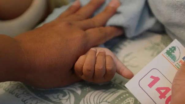 Una madre sostiene la mano de un bebé