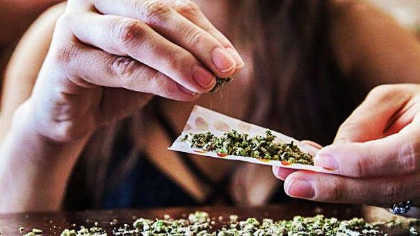 Una mujer prepara un cigarrillo de marihuana