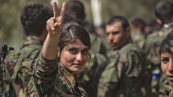 Una combatiente femenina de las FSD hace un gesto de victoria