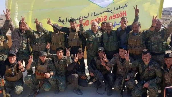 Milicianos de las Fuerzas de Siria Democrᴩca (FSD) celebran la conquista de Al Baguz junto a su bandera amarilla, en la que sobresale un mapa de Siria.