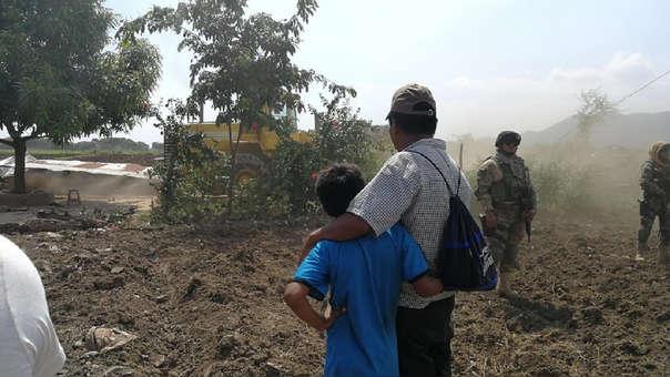 Padre e hijo miran su casa derribada